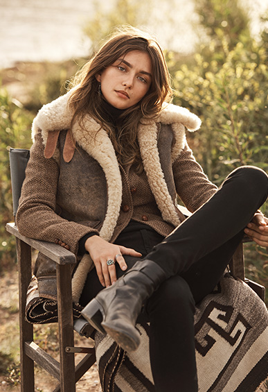 Woman seated in a chair in the outdoors wearing a shearling vest and tweed blazer