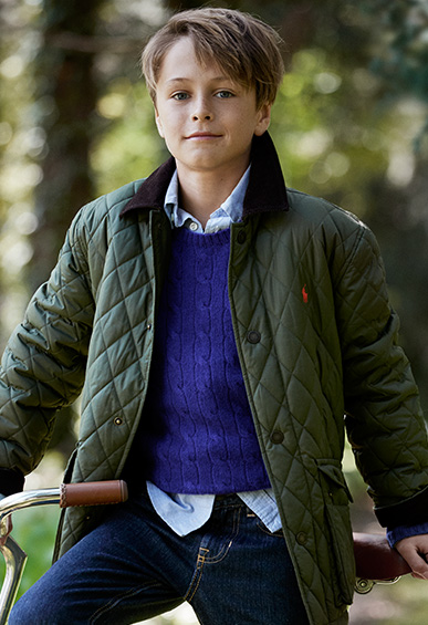 Boy wearing bright blue sweater and green quilted jacket