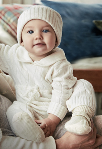 Baby in knit head-to-toe white ensemble