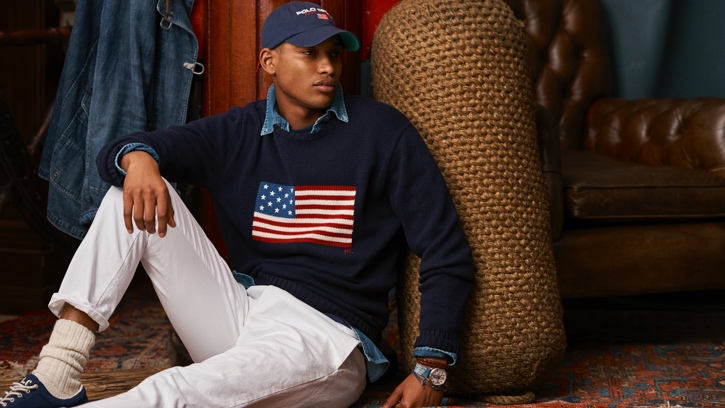 Man in navy American flag sweater & white jeans